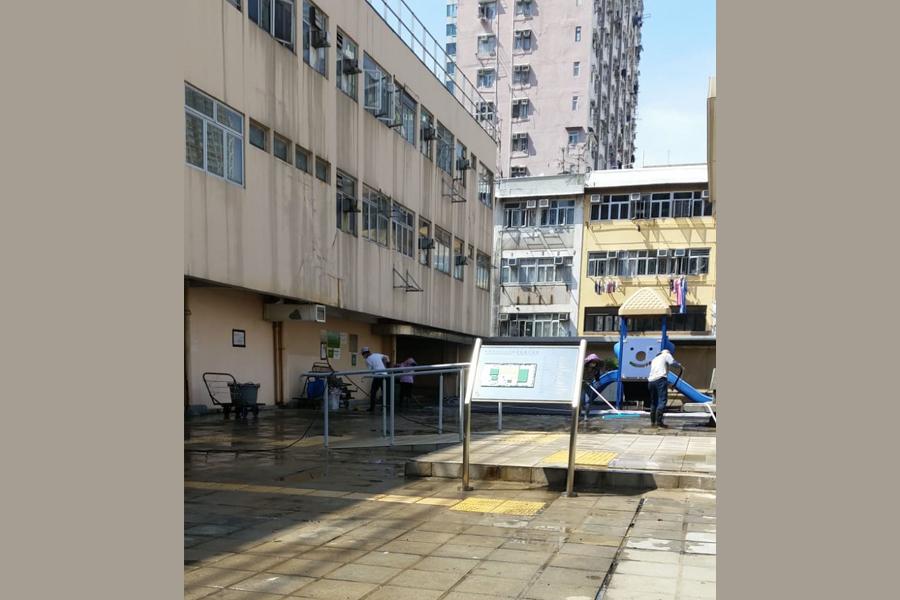 Petugas kebersihan Hong Kong terlihat membersihkan atas gedung pasar seafood Tsuen Wan.